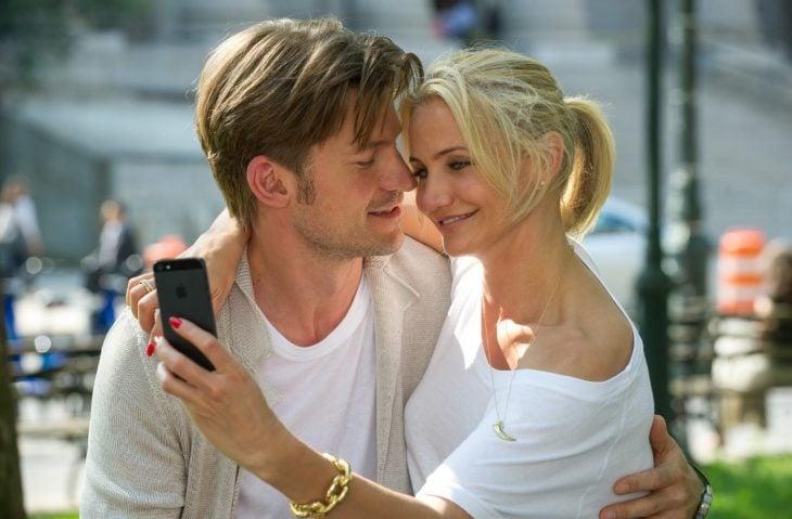 hombre de cabello corto con mujer sentada en sus piernas tomando foto de ambos