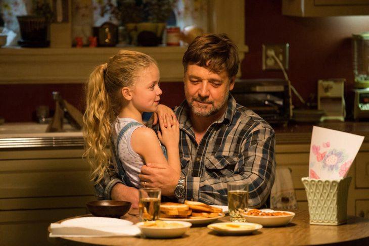 hombre con su hija en brazos en la mesa de la cocina