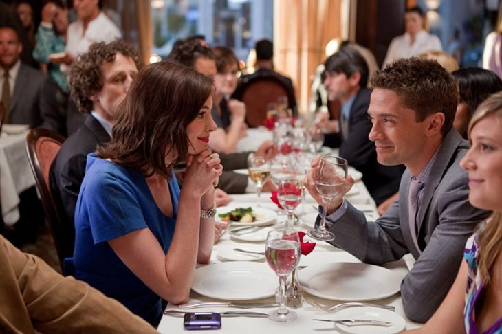 mujer de vestido azul mirando a un hombre durante la cena