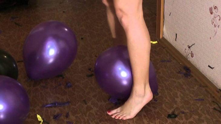 mujer tronando globos con los pies