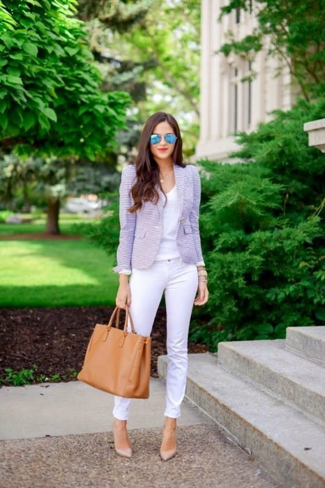 Chica vestida de blanco acompañando su outfit con un blazer en color lila