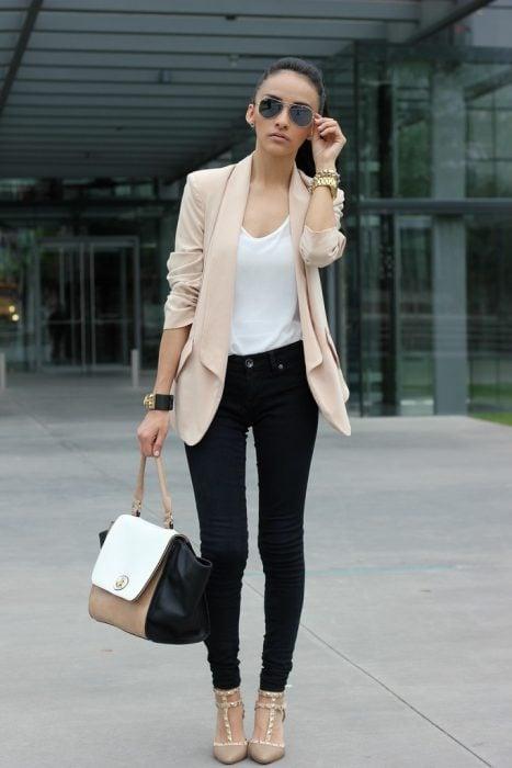 Chica usando unos jeans de color negro con un blazer en color café y blusa blanca