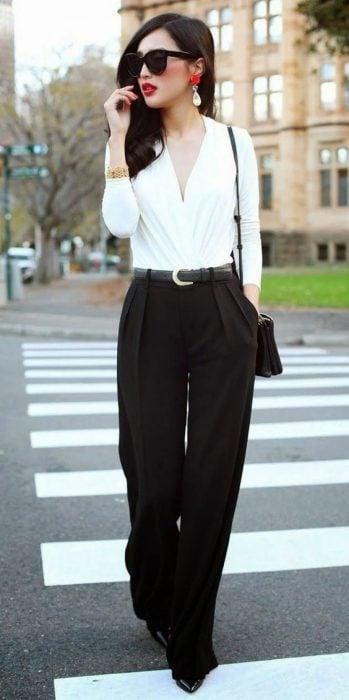 Chica usando un pantalón de color negro con una blusa de color blanco parada en medio de la calle
