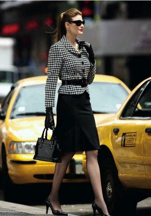 Chica usando una falda en color negro con un saco estampado y cinturón negro