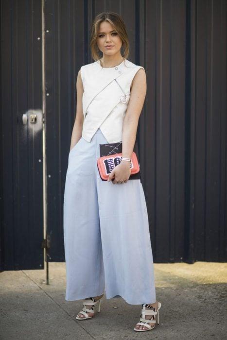 Chica usando unos pantalones holgados y una blusa en color blanco