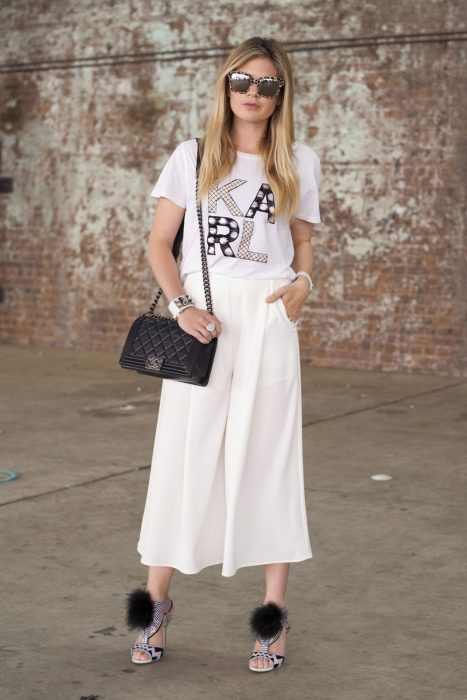 Chica usando unos pantalones acampanados en color blanco