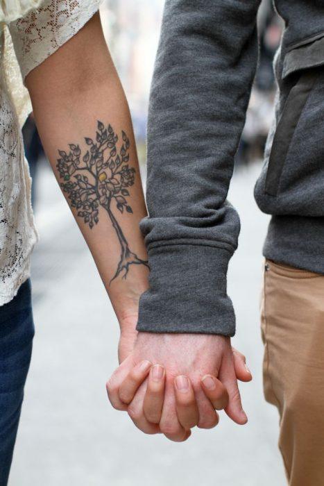 manos de pareja entrelazadas tatuaje árbol