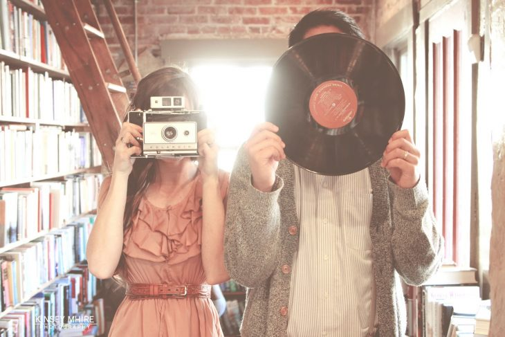pareja chica con cámara vintaje chico con disco vinil