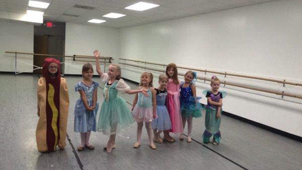 Niña vestida de hot dog para su clase de baile mientras que sus compañeras están vestidas de princesas