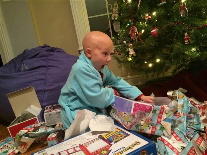 Niña que sufre de alopecia areata abriendo sus regalos de navidad
