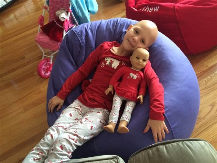Niña que sufre de alopecia areata recostada junto a su muñeca sin cabello