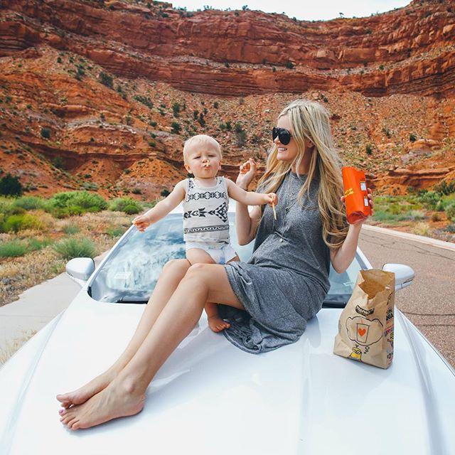 Chica y bebé sobre el cofre de un carro