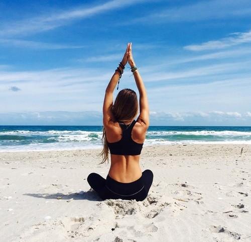 chica haciendo yoga en medio de la playa