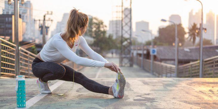 Chica estirando sus pies para ir a correr
