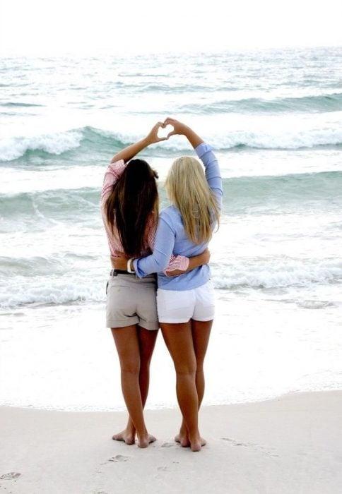 Chicas haciendo un corazón con sus manos frente a la playa