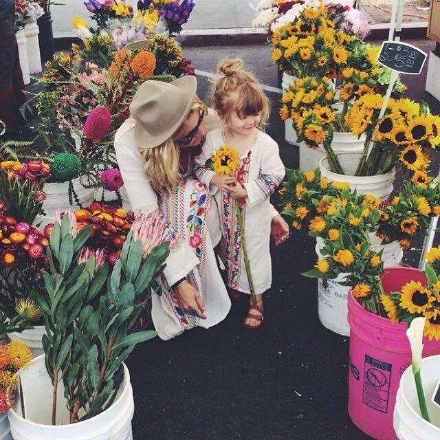 Chica y niña en una florería llena de girasoles