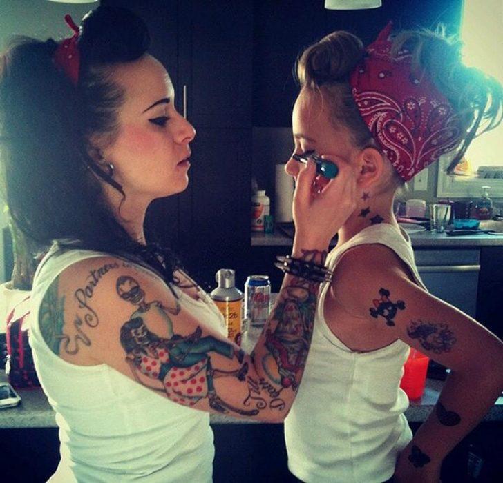 Chica maquillando a una niña chiquita