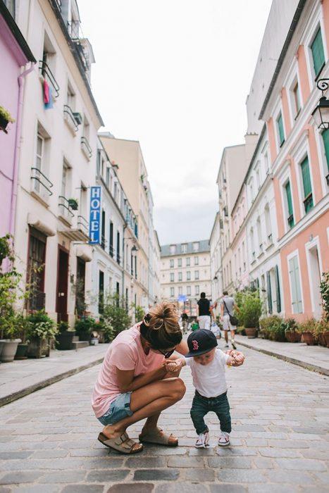 Chica sujetando a su bebé para enseñarlo a caminar