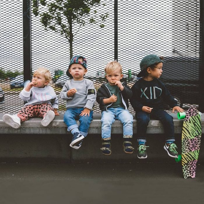 Niños sentados sobre una banca comiendo