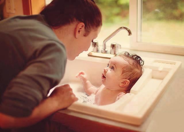 Mamá dandole un baño a su bebé en el lavabo de la cocina