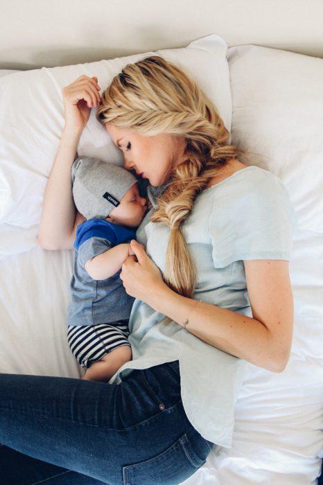 Chica recostada junto a su bebé