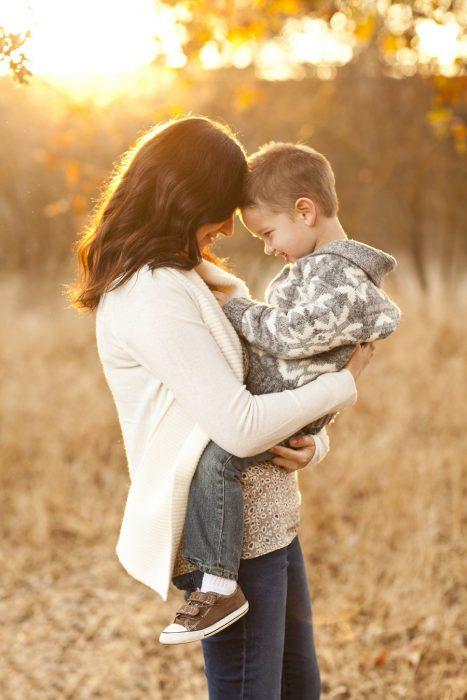 Madre abrazando a su hijo mientras están en medio de los árboles