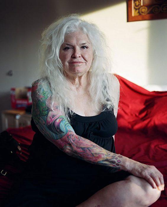 Señora de cabello blanco y largo con el brazo tatuado