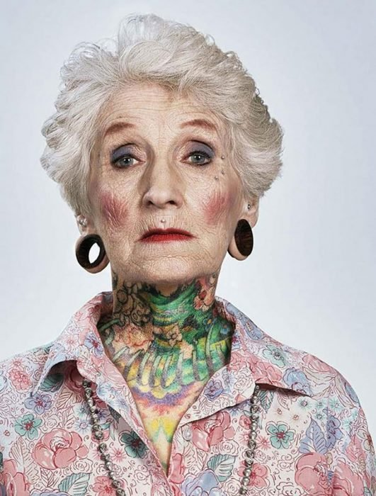 Mujer con tatuajes de edad mayor y expansiones en las orejas