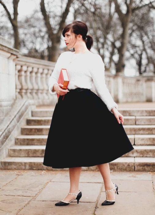 Chica parada bajo unos escalones usando falda negra, blusa blanca y tacones de 6 centímetros