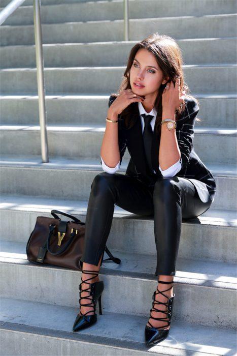 Chica sentada en unas escaleras pensando y mirando hacia la nada