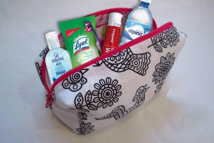 Bolsa cosmetiquera con distintos implementos de viaje