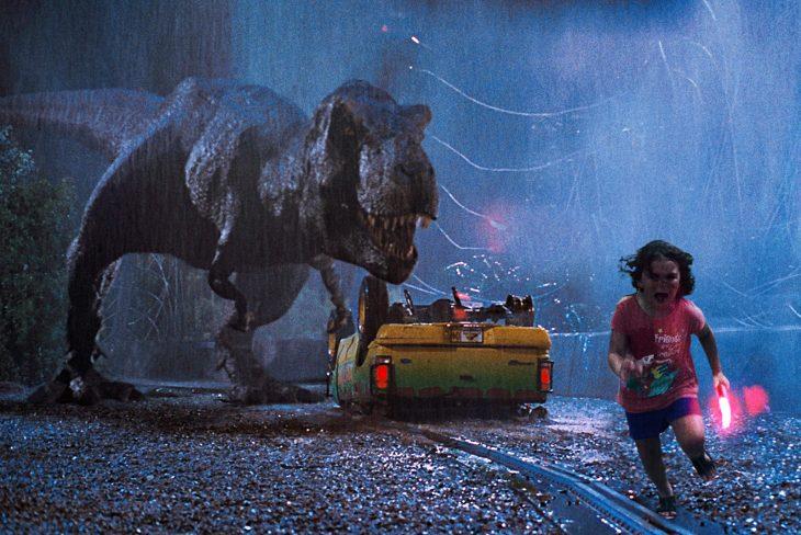 niña corriendo con dinosaurio atrás