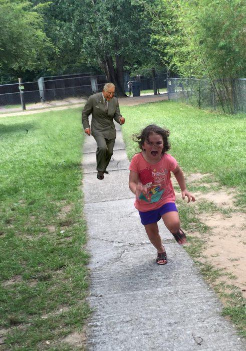 niña corriendo con imagen del príncipe carlos detrás