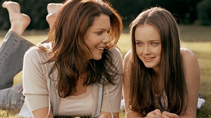 Escena de la serie gilmore gils chicas conversando mientras están recostadas en el pasto