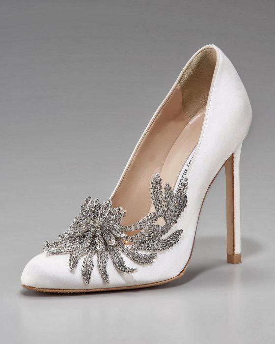 Zapatos de novia color blanco con un adorno en color plata