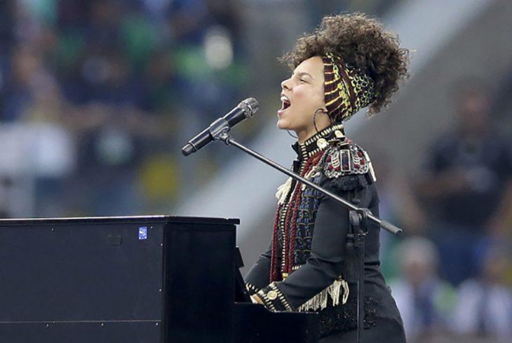 Mujer sentada en piano tocando y cantando
