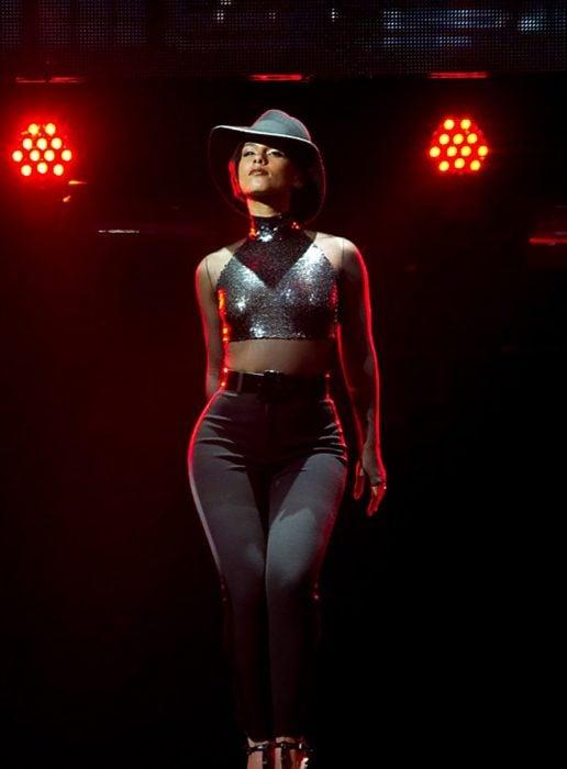 mujer pantalon negro y crop top con sombrero figura de pera