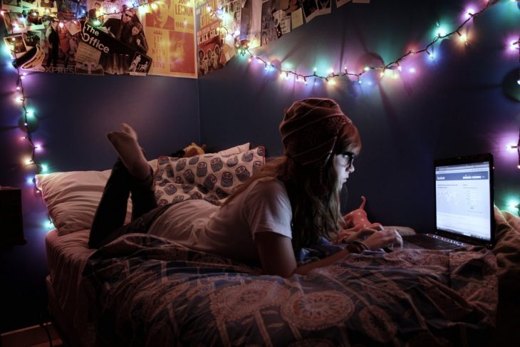 mujer acostada en la cama con lentes y gorro