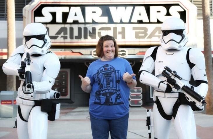 Mujer de camisa azul sonríe al lado de soldados Star Wars
