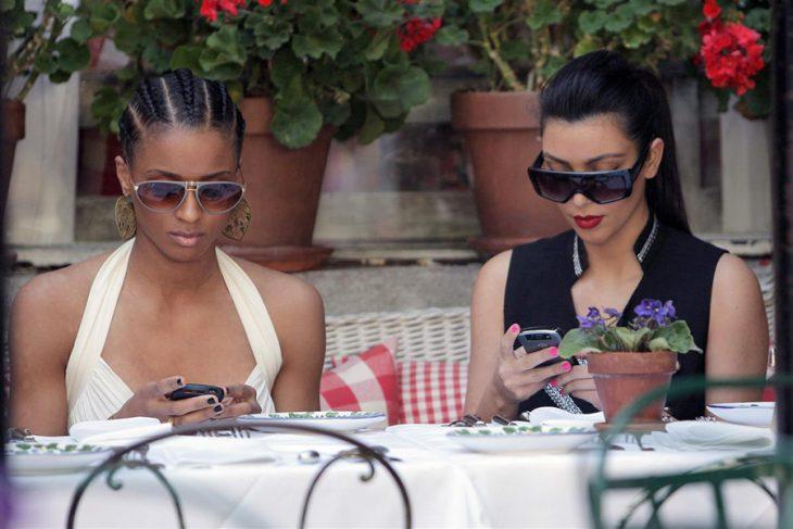 par de mujeres sentadas en una mesa usando sus teléfonos celulares