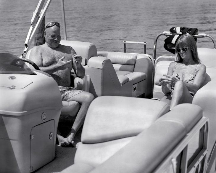 mujer y hombre sentados en un bote mirando sus manos