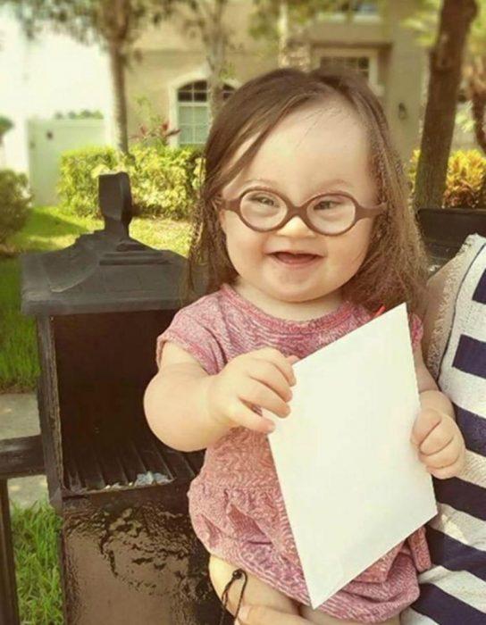 niña en brazos con lentes y carta en un buzón