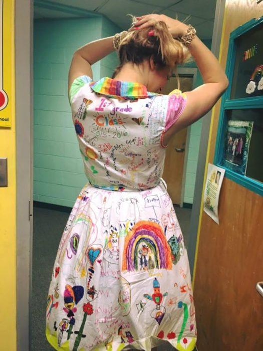 mujer rubia de espaldas enseña su vestido dibujado por niños