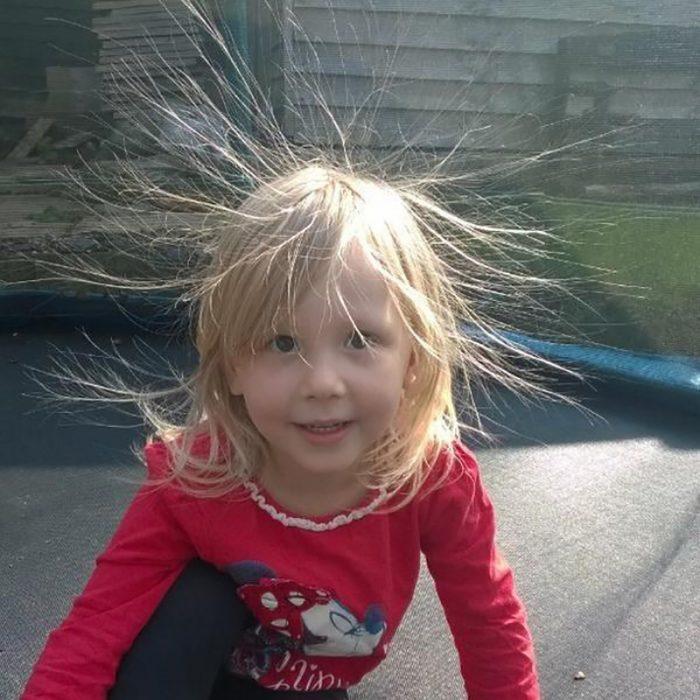 niña rubia sentada en brincolin con cabello frizado