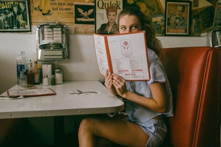 mujer rubia en restaurante con menú