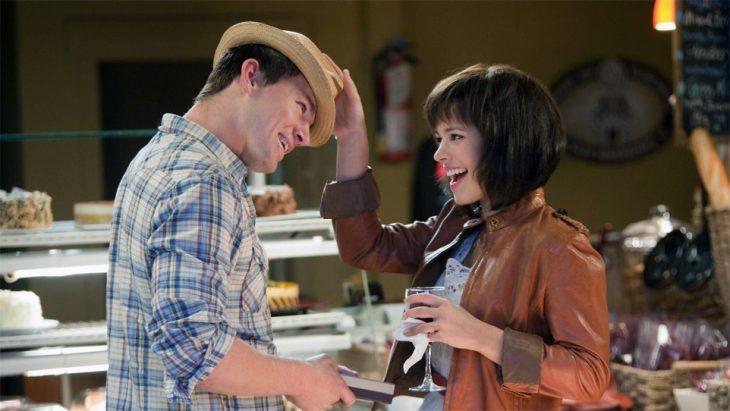 pareja en un café jugando con sombrero y sonriendo
