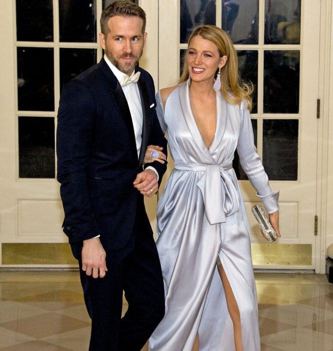 mujer rubia con bata azul cielo y hombre con traje la toma del brazo