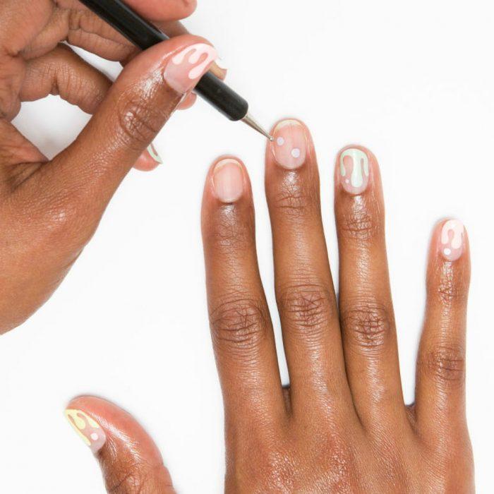 manos de mujer morena con uñas de nieve derritiendose