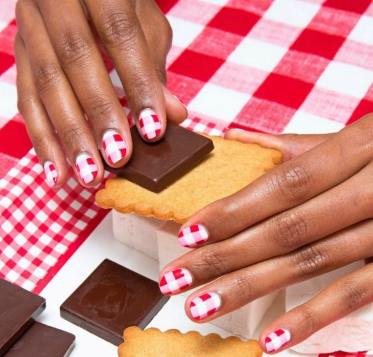 manos de mujer morena con diseño de cuadros rojos blancos y rosas y galletas