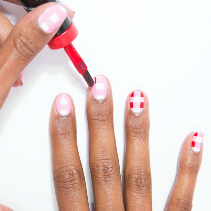manos de mujer morena con diseño de cuadros rojos blancos y rosas